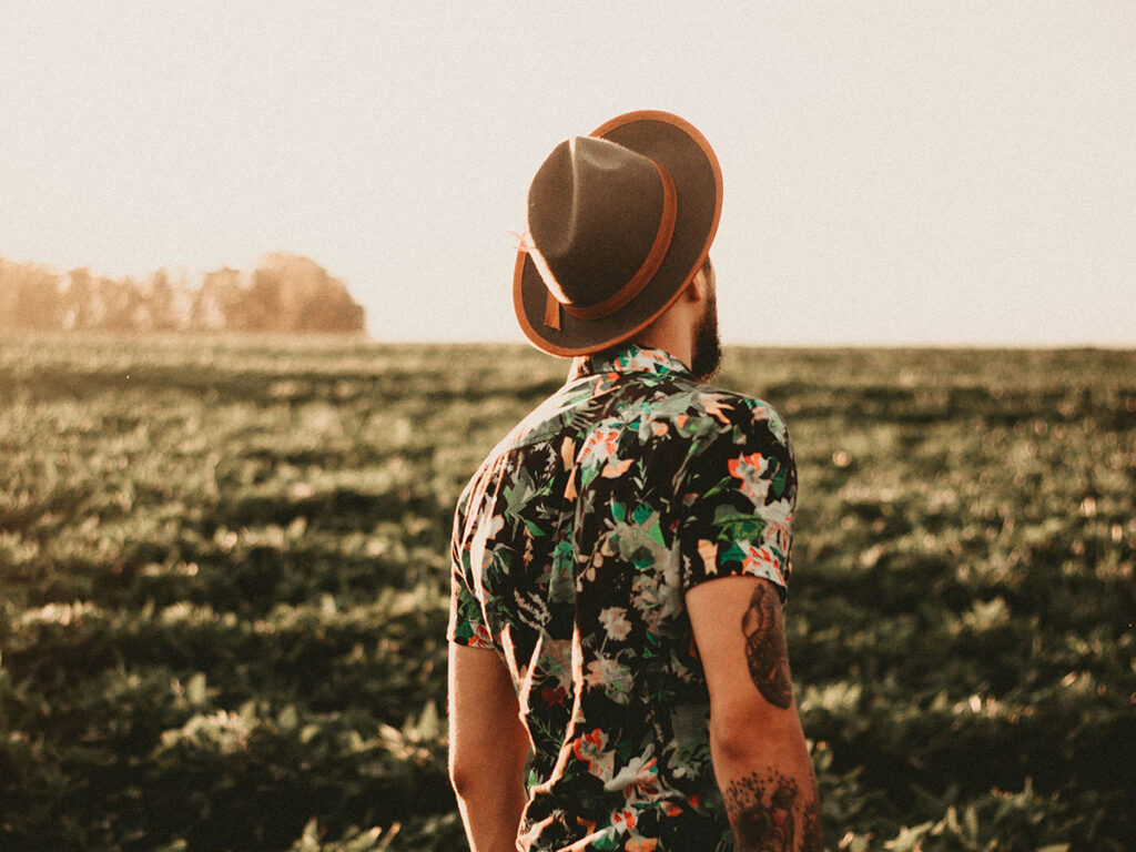 image of stylish man in hat and shirt with cool design in a field.