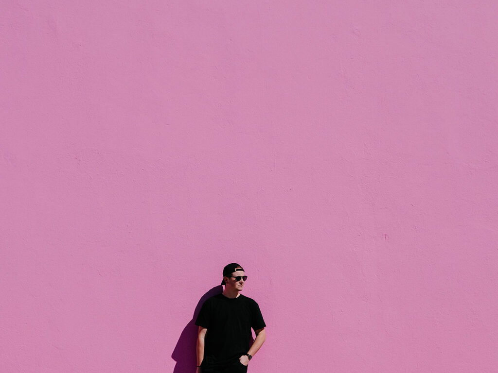 image of man looking cool with a large pink background.