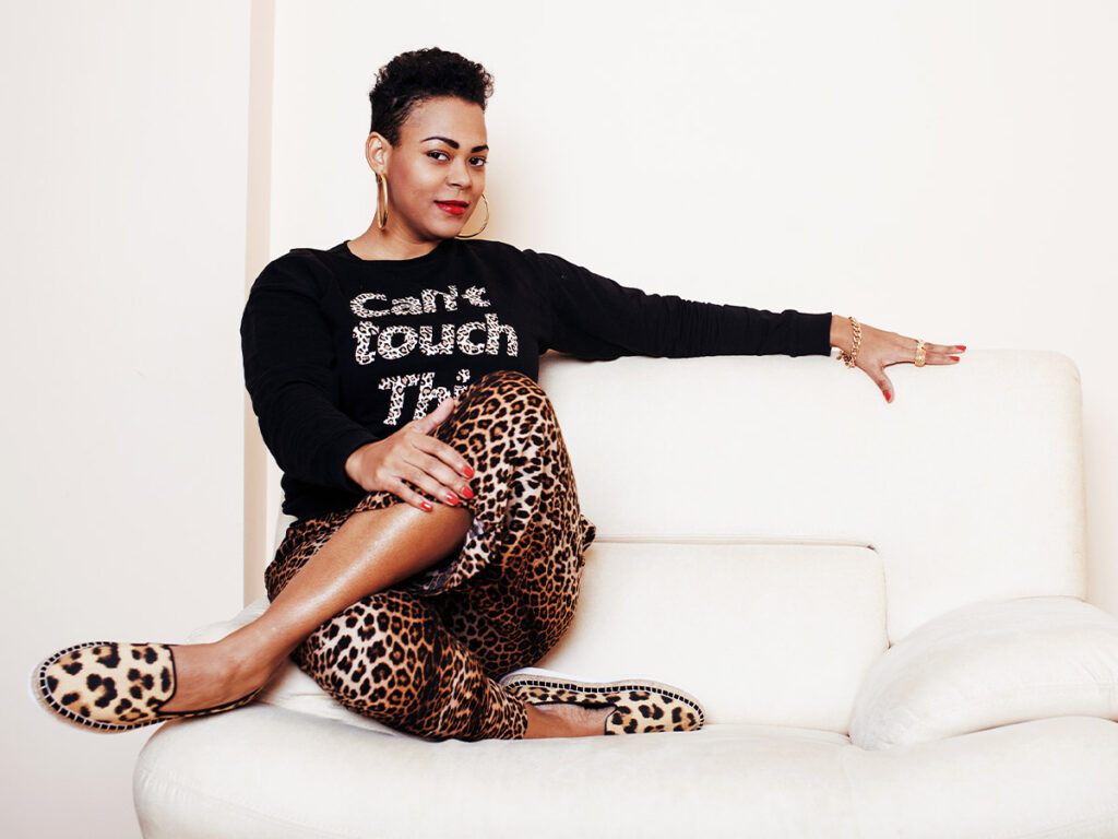 Woman wearing leopard print pants and shoes with a black graphic top.